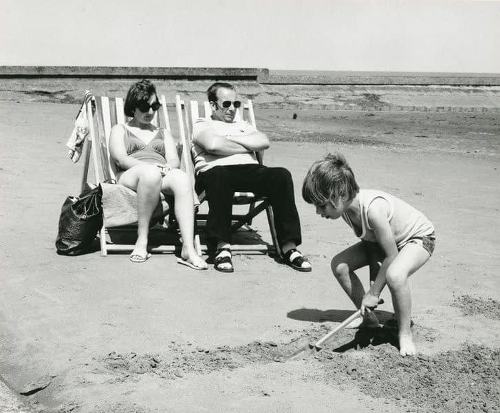 Description : 'Family Holiday', Black and white photograph mounted on card, by John Heywood, 1979.