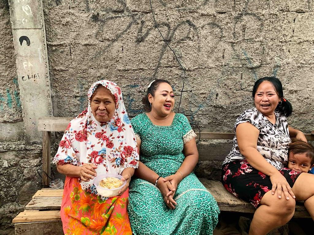 Trois femmes discutant et riant sur un banc
